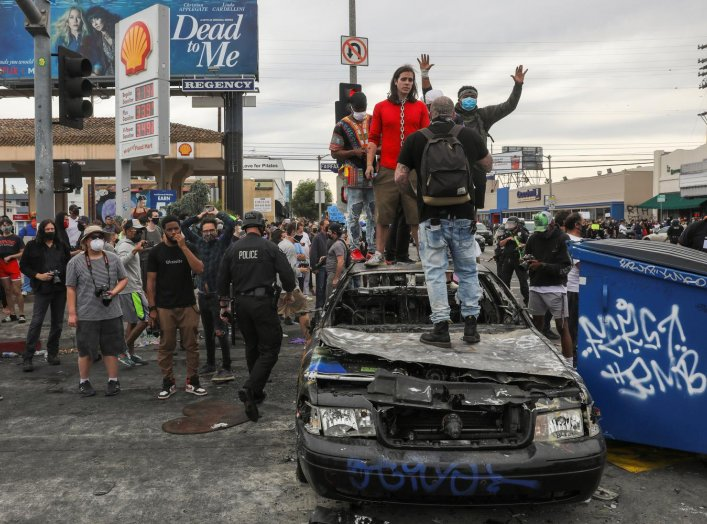 Demonstrators stand on top of a burned out police car during a protest against the death in Minneapolis police custody of George Floyd, in Los Angeles, California, U.S., May 30, 2020. REUTERS/Patrick T. Fallon
