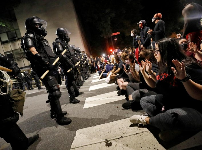 Protesters sit in the street facing a line of riot policemen during nationwide unrest following the death in Minneapolis police custody of George Floyd, in Raleigh, North Carolina, U.S. May 31, 2020. REUTERS/Jonathan Drake