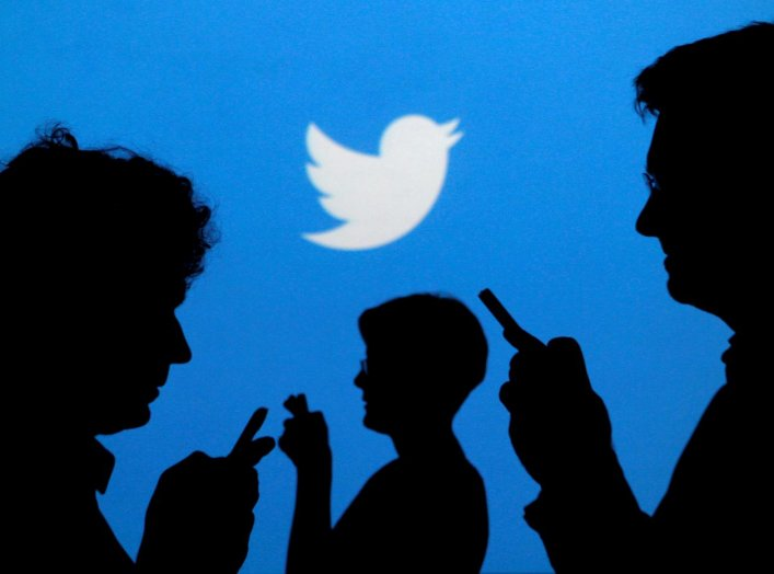 People holding mobile phones are silhouetted against a backdrop projected with the Twitter logo in this illustration picture taken in Warsaw September 27, 2013. REUTERS/Kacper Pempel/Illustration