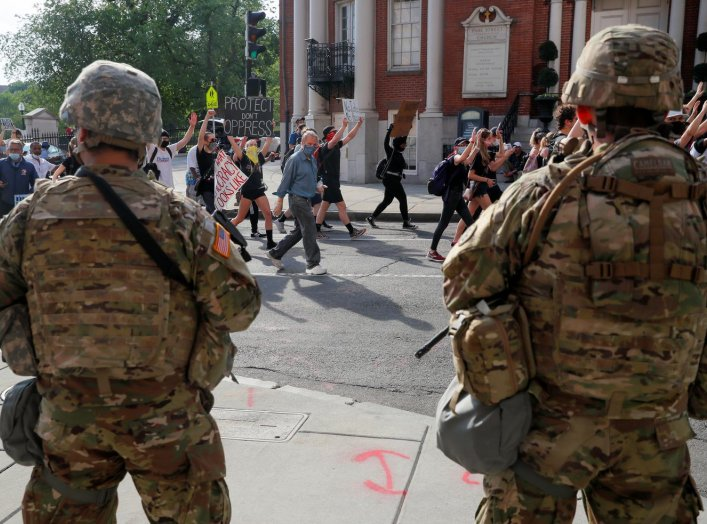 Massachusetts National Guard members look on as demonstrators march during a protest following the death in Minneapolis police custody of George Floyd, in Boston, Massachusetts, U.S., June 3, 2020. REUTERS/Brian Snyder