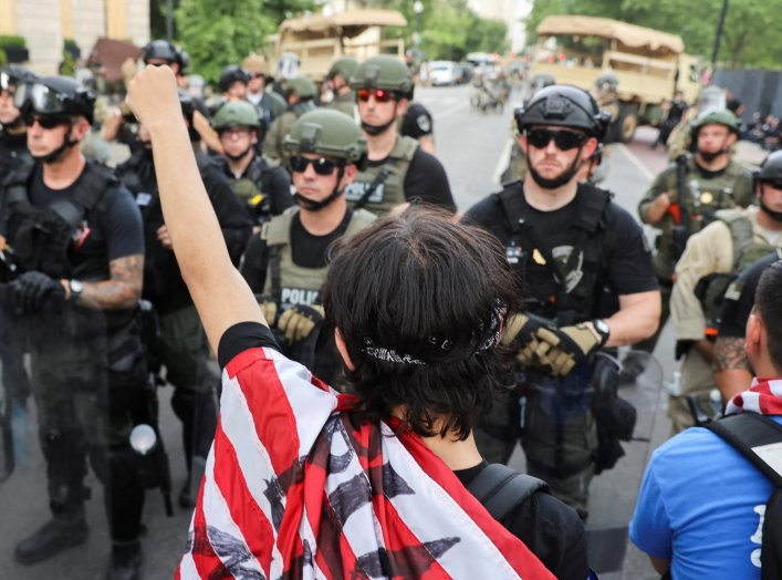 Demonstrators stand in front of law enforcement officers during a protest against the death in Minneapolis police custody of George Floyd, near the White House in Washington, U.S., June 3, 2020. REUTERS/Jonathan Ernst