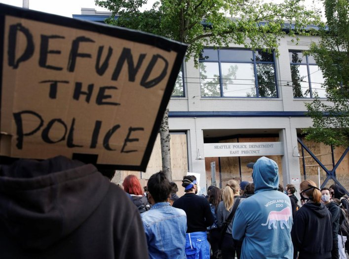 """A protester holds a sing that reads """"defund the police"""" after Seattle Police vacated the department's East Precinct and people continue to rally against racial inequality and the death in Minneapolis police custody of George Floyd, in Seattle, Washington,"""