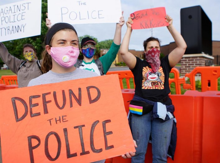 A protester holds a sign calling for the defunding of the police during a protest against the police brutality of a man hit by a Florissant detective and the death in Minneapolis police custody of George Floyd, in Florissant, Missouri, U.S. June 10, 2020.