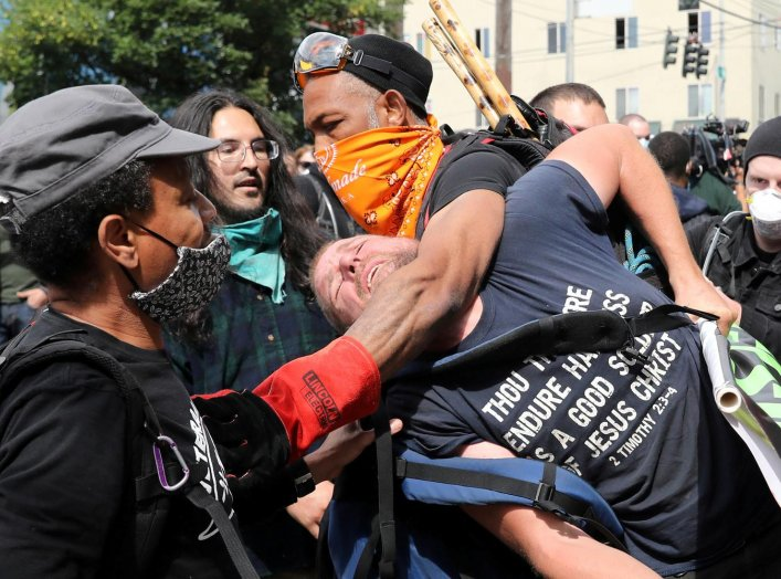 Protesters remove a man from the protest because he was bothering other protesters at the self-proclaimed Capitol Hill Autonomous Zone (CHAZ) during a protest against racial inequality and call for defunding of Seattle police, in Seattle, Washington, U.S.