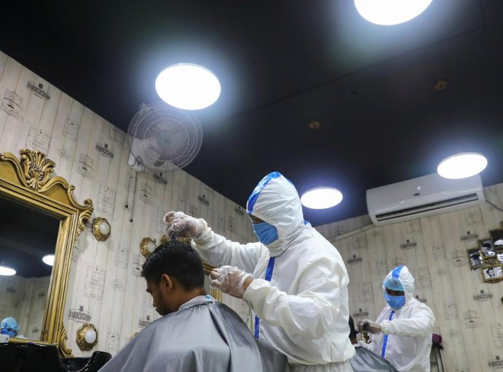 Barbers wearing protective suits and face masks provide hair cut service to the customers inside a salon amid the coronavirus disease (COVID-19) outbreak, in Dhaka, Bangladesh June 16, 2020. REUTERS/Mohammad Ponir Hossain