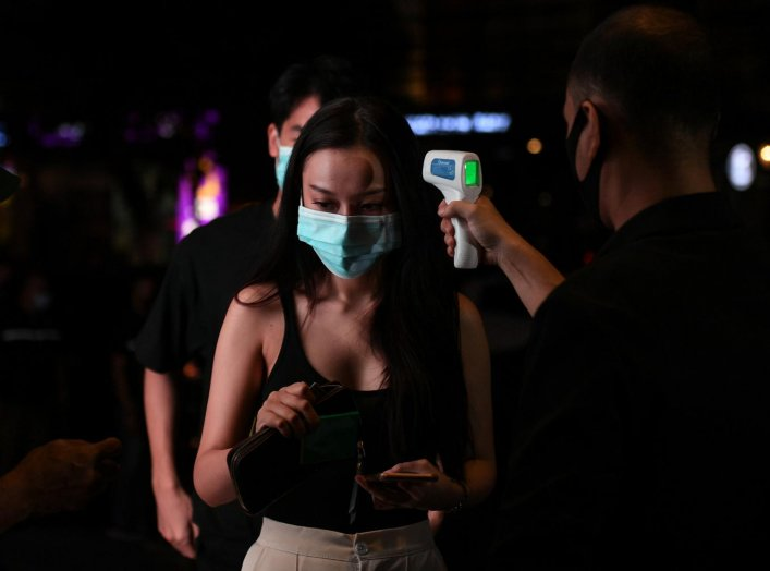 A woman has her temperature checked before entering a bar after the Thai government eased isolation measures and introduced social distancing to prevent the spread of the coronavirus disease (COVID-19), as bars and nightclubs are reopened nationwide, in B