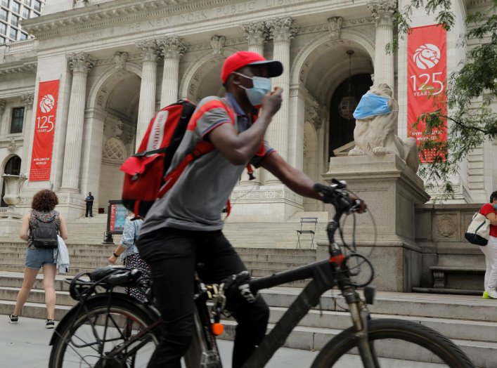 A large mask hangs on the face of a lion statue standing outside of the main branch of the New York Public Library in the Manhattan borough of New York City, U.S., July 1, 2020. REUTERS/Lucas Jackson