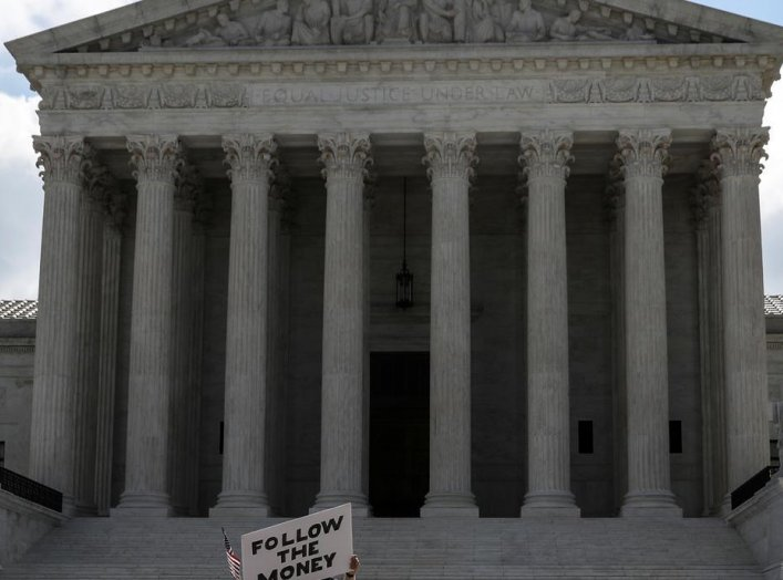 """A demonstrator holds a sign reading """"follow the money"""" in anticipation of a U.S. Supreme Court ruling on U.S. President Donald Trump's bid to block his financial records from being obtained by third parties, outside the court in Washington, U.S., July 9,"""