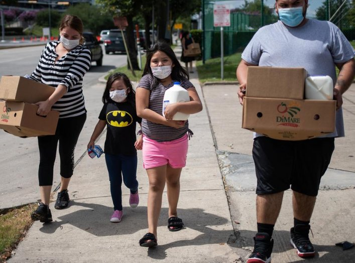 Members of the Rodriguez family carry groceries distributed by the Houston Food Bank for residents affected by the economic fallout caused by the coronavirus disease (COVID-19) pandemic in Houston, Texas, U.S., July 18, 2020. REUTERS/Adrees Latif