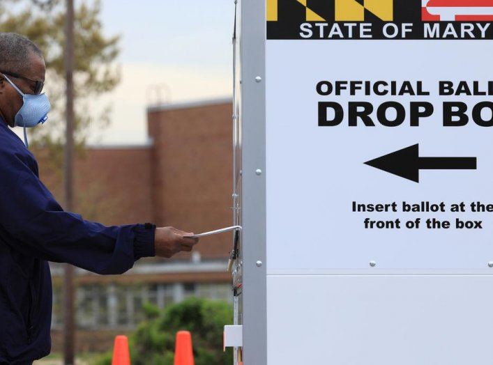 FILE PHOTO: A resident drops off a mail-in ballot at the Edmondson Westside High School Polling site in Baltimore, Maryland, U.S., April 28, 2020. REUTERS/Tom Brenner/File Photo