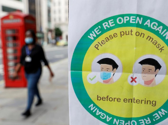 A sign urging to wear face masks is seen outside a shop, under the new rules that enforce wearing face coverings in enclosed public spaces, amid the coronavirus disease (COVID-19) outbreak, in central London, Britain July 24, 2020. REUTERS/John Sibley