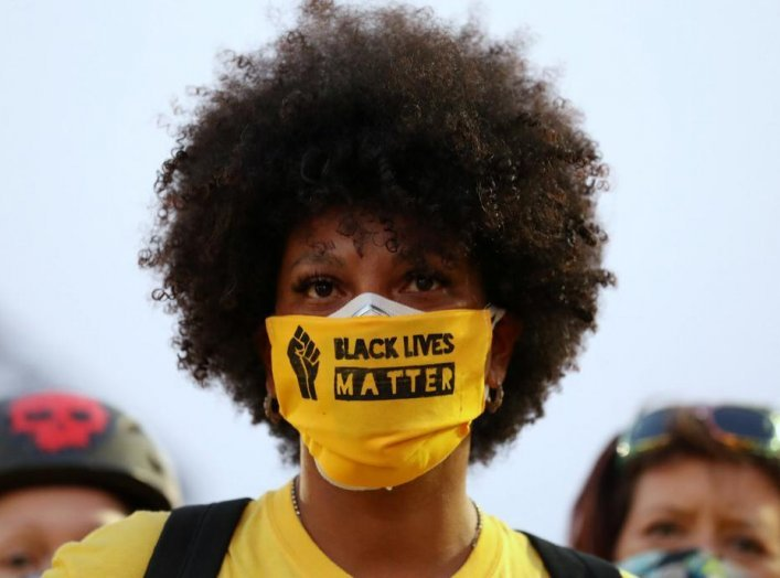 "A protester with the ""Black Lives Matter"" slogan printed on her face mask joins a protest against racial inequality and police violence in Portland, Oregon, U.S., July 26, 2020. REUTERS/Caitlin Ochs"