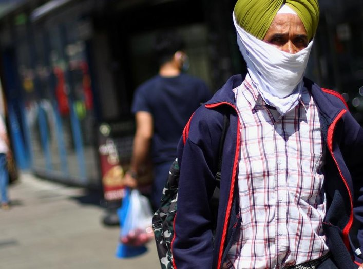 A man wears a piece of cloth as a protective mask as he walks down a street following the coronavirus disease (COVID-19) outbreak, in Ilford, London, Britain July 29, 2020. REUTERS/Hannah McKay