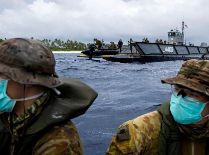 Australian Army soldiers from 2nd Battalion, the Royal Australian Regiment, launch a zodiac inflatable boat from one of HMAS Canberra's Landing Craft to deliver food and supplies to three stranded mariners from the Federated States of Micronesia following