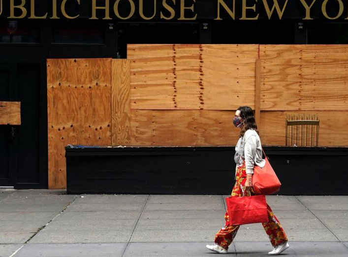 A woman walks past a shuttered bar following the coronavirus (COVID-19) disease outbreak in the Manhattan borough of New York City, New York, U.S., August 7, 2020. REUTERS/Carlo Allegri
