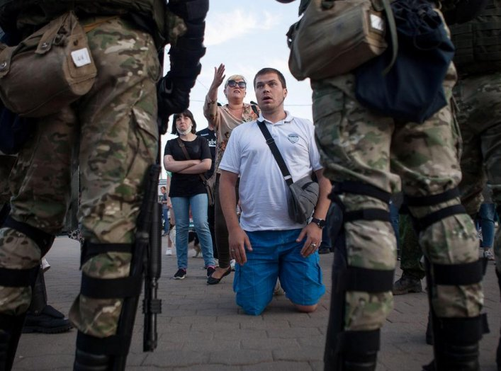 People talk to Belarusian law enforcement officers near the site where a protester died on August 10 during a rally following the presidential election in Minsk, Belarus August 11, 2020. REUTERS/Stringer