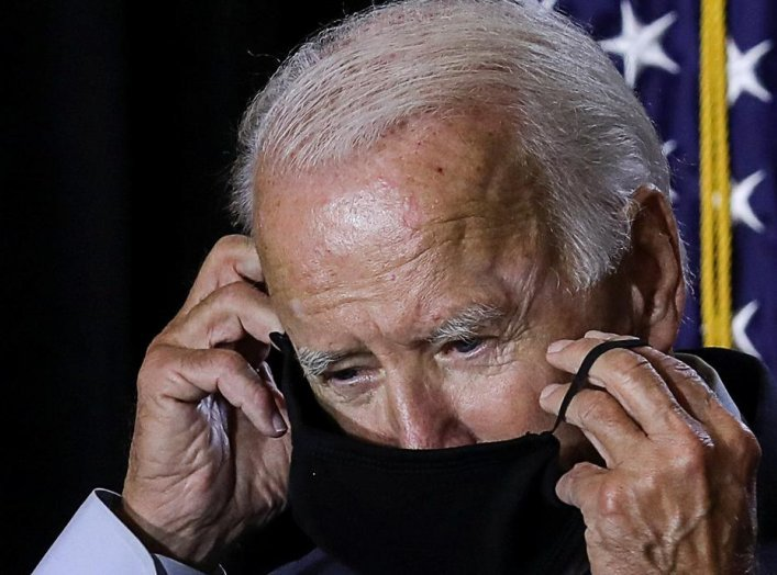 Democratic U.S.presidential candidate Joe Biden adjusts his protective face mask as he calls for the mandatory wearing of masks while speaking to reporters following a briefing on the coronavirus disease (COVID-19) pandemic with public health experts duri