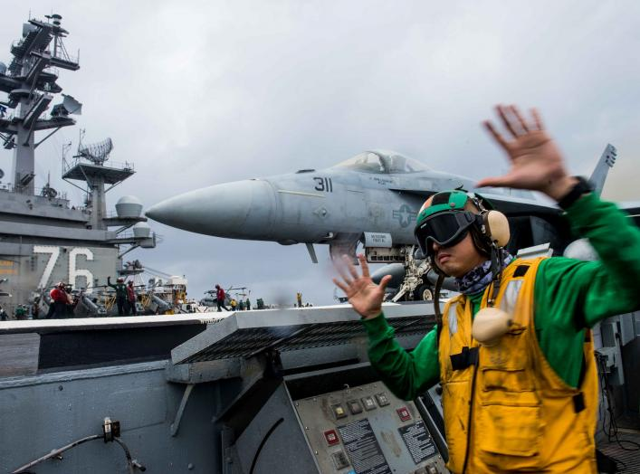 PHILIPPINE SEA (July 4, 2018) Aviation Boatswain's Mate (Equipment) 1st Class Clayton Hudson, from Fairfield, Calif., signals for the launch of an F/A-18E Super Hornet assigned to Strike Fighter Squadron (VFA) 115 on the flight deck of the Navy's forward-