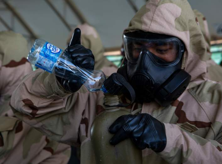U.S. Marine Corps Cpl. Anthony Calderon, a systems administrator attached to Special Purpose Marine Air Ground Task Force Crisis Response-Central Command, fills his canteen during chemical, biological, radiological and nuclear defense training in Kuwait,