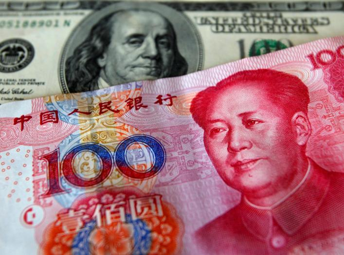 FILE PHOTO: A yuan banknote is displayed next to a U.S. dollar banknote (back) for the photographer at a money changer inside the Taoyuan International Airport March 18, 2010. REUTERS/Nicky Loh/File Photo