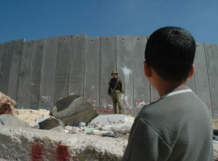 English: A Palestinian boy and Israeli soldier in front of the Israeli West Bank Barrier.