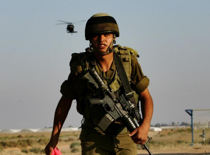 An Israeli soldier watches a chopper land on a military area in Kerem Shalom at the border with Gaza June 28, 2006. Israel fired artillery shells into the northern Gaza Strip on Wednesday as troops and tanks prepared to widen an offensive aimed at forcing