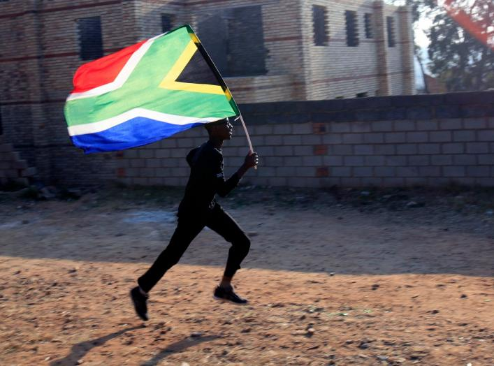 A worker runs with the South African flag inside the Soccer City stadium in Soweto, Johannesburg June 10, 2010. The stadium will host the opening and final games of the 2010 FIFA Soccer World Cup which kicks off on June 11. REUTERS/Radu Sigheti (SOUTH AFR