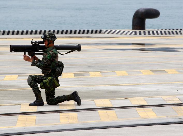 A soldier stands guard with his weapon during the 2011 Jinhua exercise at the Port of Taipei in New Taipei City, northern Taiwan, June 29, 2011. Taiwan on Wednesday hosted a disaster and anti-terrorism drill that involved more than 1000 people from the po