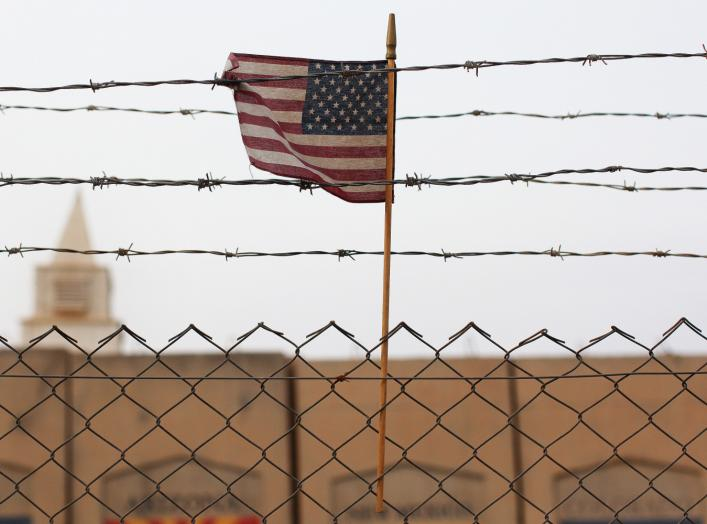 An American flag is seen behind barbed wire at the former U.S. Sather Air Base near Baghdad, Iraq December 14, 2011.