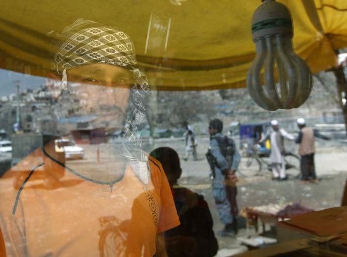 A shopkeeper stands inside a shop as people are reflected on a window panel in Kabul April 8, 2012. REUTERS/Omar Sobhani