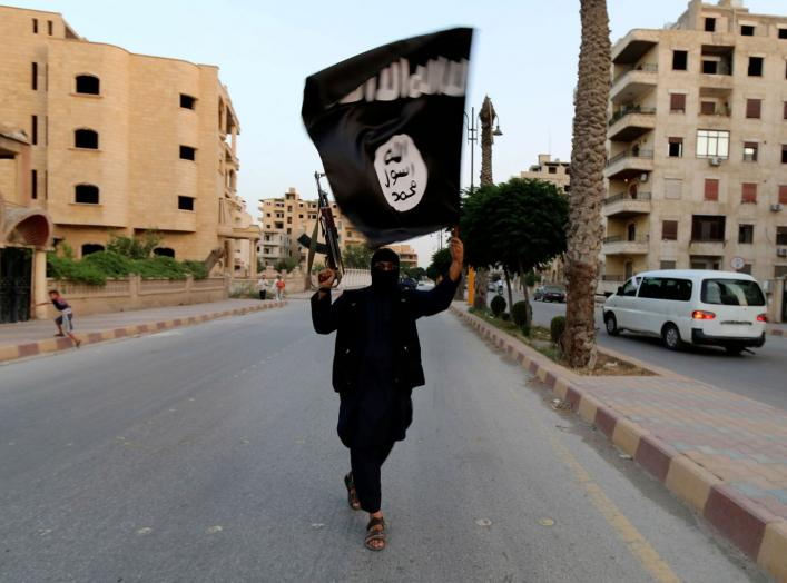 "A member loyal to the Islamic State in Iraq and the Levant (ISIL) waves an ISIL flag in Raqqa June 29, 2014. The offshoot of al Qaeda which has captured swathes of territory in Iraq and Syria has declared itself an Islamic ""Caliphate"" and called on factio"