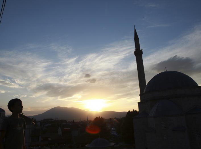 Image: A boy looks at the sky near an orthodox church and a mosque in Prizren, southwest from capital Pristina August 20, 2014. REUTERS/Hazir Reka
