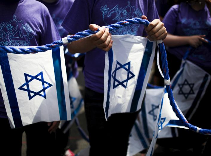 People hold a rope with Israeli national flags attached to it during the 51st annual Israel parade in Manhattan, New York May 31, 2015. REUTERS/Eduardo Munoz