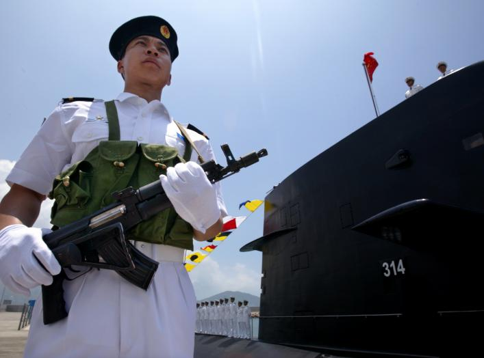 "A Chinese Naval officer stands guard beside a submarine at the Ngong Shuen Chau Naval Base in Hong Kong April 30, 2004. China will expand the membership of the military's top decision-making body to ""suit the needs of modern warfare"" if Taiwan declares in"