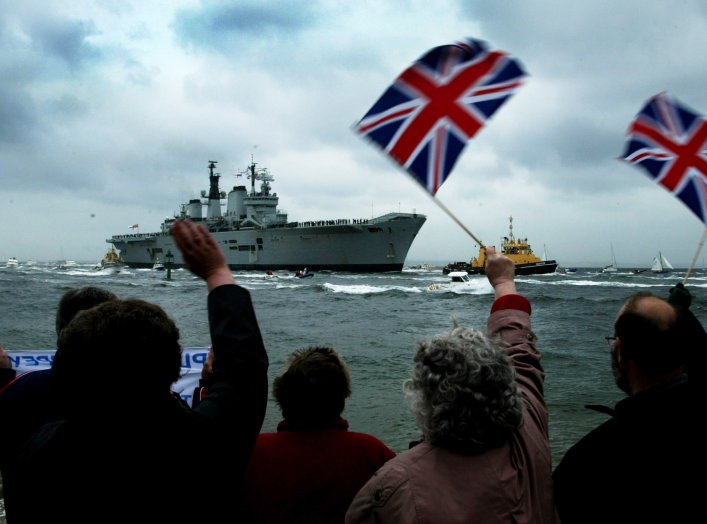 People wave as the flagship of Britain's Royal Navy HMS (Her Majesty's Ship) Ark Royal approaches Portsmouth Harbour on the coast of southern England, after operations in the Gulf conflict, May 17, 2003. REUTERS/Michael Crabtree