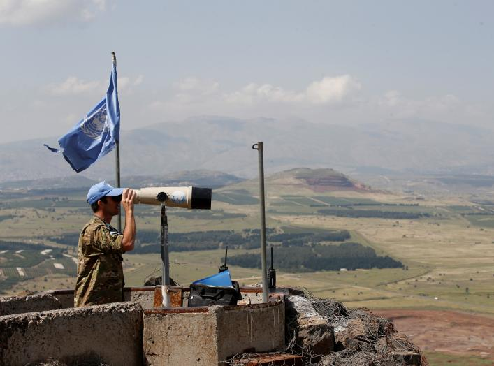 A United Nations Truce Supervision Organisation military observer uses binoculars near the border with Syria in the Israeli-occupied Golan Heights, Israel May 11, 2018. REUTERS/Baz Ratner