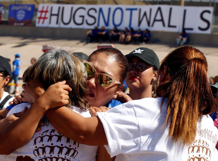 Mexicans (white shirts), who live in Mexico, hug relatives (blue shirts), who live in the U.S., during the Hugs Not Walls event on the border between Ciudad Juarez, Mexico and El Paso, U.S., May 12, 2018. REUTERS/Jose Luis Gonzalez