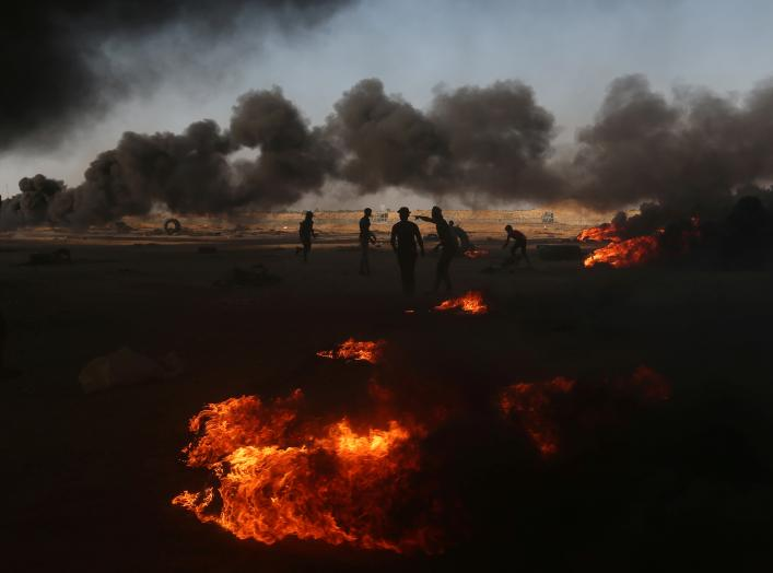 Palestinian demonstrators are seen as smoke rises from burning tires during a protest marking the 70th anniversary of Nakba, at the Israel-Gaza border in the southern Gaza Strip May 15, 2018. REUTERS/Ibraheem Abu Mustafa