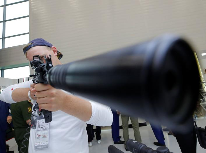 """A participant holds a rifle during the annual international military-technical forum """"ARMY"""" at Patriot Expocentre in Moscow Region, Russia August 21, 2018. REUTERS/Maxim Shemetov"""