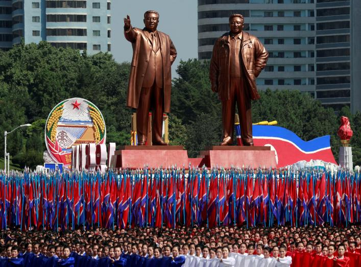People carry flags in front of statues of North Korea founder Kim Il Sung (L) and late leader Kim Jong Il during a military parade marking the 70th anniversary of North Korea's foundation in Pyongyang, North Korea, September 9, 2018. REUTERS/Danish Siddiq