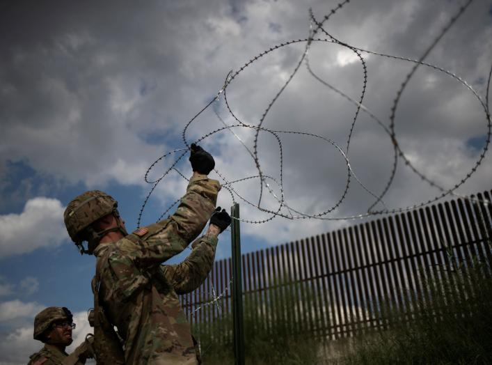 The border wall is seen in the background as U.S. Army soldiers install concertina wire along the United States - Mexico border in Hidalgo, Texas, U.S., November 8, 2018. Picture taken on November 8, 2018. REUTERS/Adrees Latif