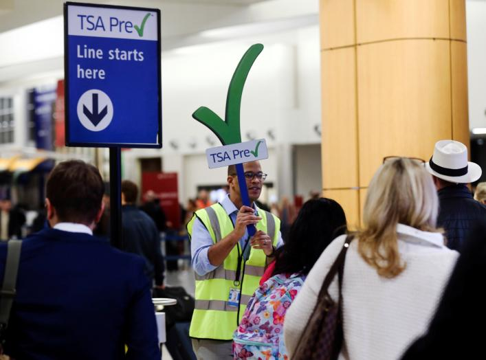 A man guides passengers towards a Transportation Security Administration (TSA) PreCheck security checkpoint at Hartsfield-Jackson Atlanta International Airport amid the partial federal government shutdown, in Atlanta, Georgia, U.S., January 18, 2019.