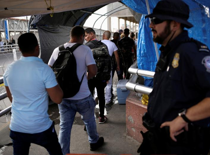 A U.S. Customs and Border Protection (CBP) agent looks at Cuban migrants entering into the United States to claim asylum, at the Santa Fe border crossing bridge in Ciudad Juarez, Mexico September 9, 2019. REUTERS/Jose Luis Gonzalez
