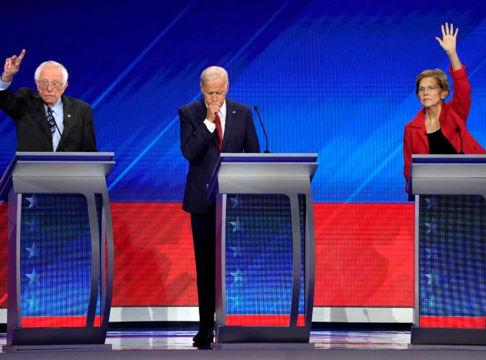 Former Vice President Joe Biden stands between Senator Bernie Sanders (L) and Senator Elizabeth Warren (R) as they both raise their hands to answer a question at the 2020 Democratic U.S. presidential debate in Houston, Texas, U.S. September 12, 2019.