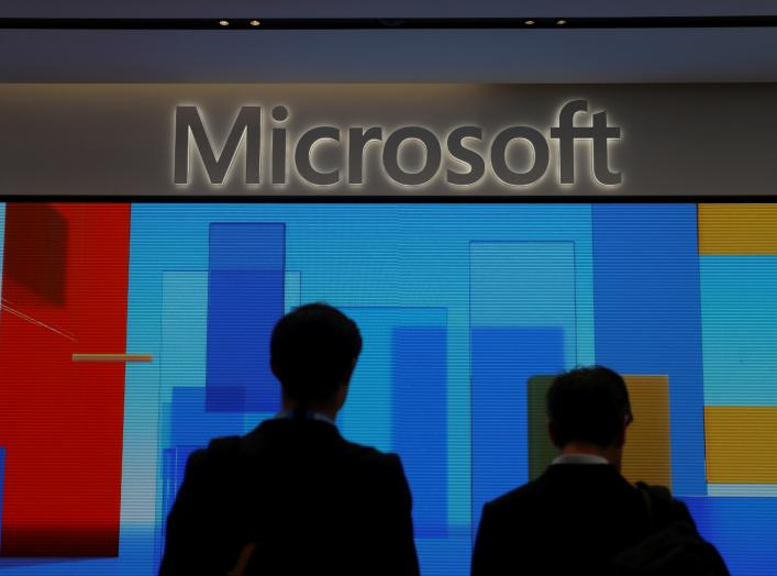 FILE PHOTO: Visitors stand in front of a display screen at Microsoft's new Oxford Circus store ahead of its opening in London, Britain July 9, 2019. REUTERS/Simon Dawson/File Photo
