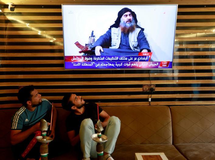FILE PHOTO: Iraqi youth watch the news of Islamic State leader Abu Bakr al-Baghdadi death, in Najaf, Iraq October 27, 2019. REUTERS/Alaa al-Marjani/File Photo