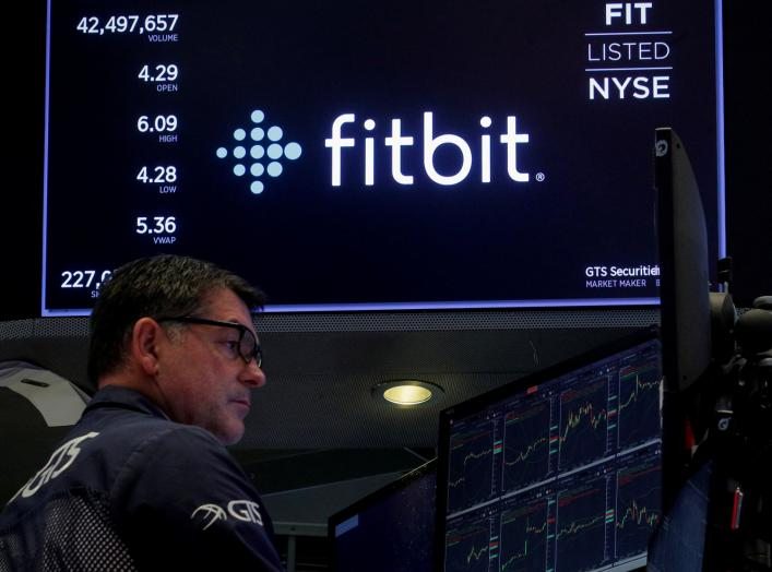 A trader works at his post as the logo for wearable device maker Fitbit Inc. is displayed on a screen on the floor of the New York Stock Exchange (NYSE) as begins public trading in New York, U.S., October 28, 2019. REUTERS/Brendan McDermid