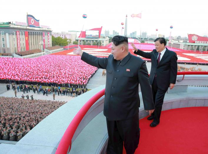 North Korean leader Kim Jong Un (L) and senior Chinese Communist Party official Liu Yunshan (R) wave during celebration of the 70th anniversary of the founding of the ruling Workers' Party of Korea, in this undated photo released by North Korea's Korean C