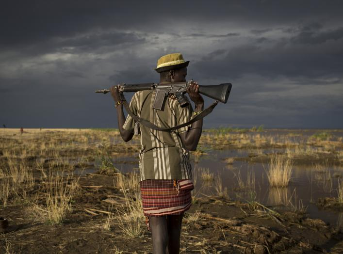 An armed Turkana man walks towards the shores of Lake Turkana near a temporary fishing camp some kilometres from Todonyang near the Kenya-Ethiopia border in northwestern Kenya October 12, 2013. The Turkana are traditionally nomadic pastoralists, but they