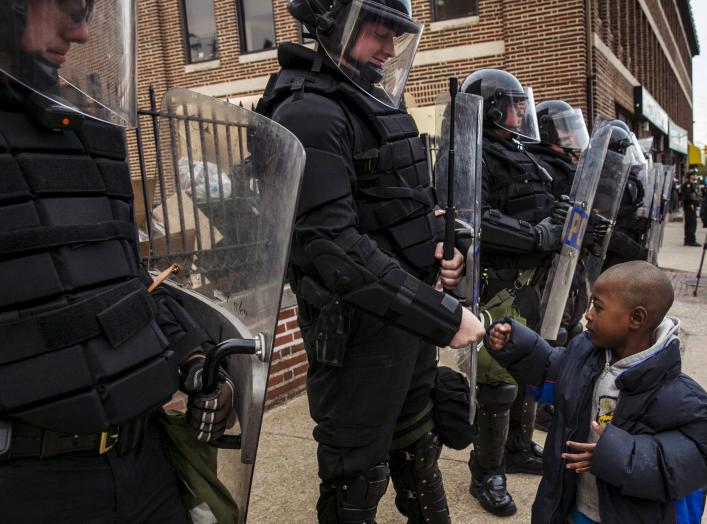 A young boy greets police officers in riot gear during a march in Baltimore, Maryland May 1, 2015 following the decision to charge six Baltimore police officers -- including one with murder -- in the death of Freddie Gray, a black man who was arrested and
